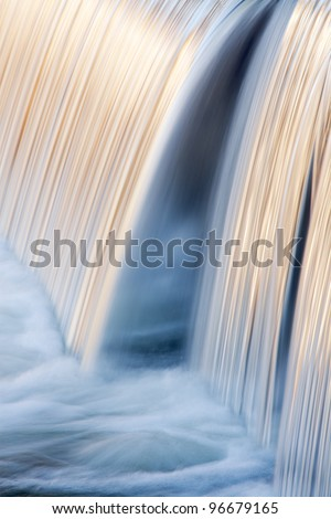 Portage Creek Cascade captured with motion blur and illuminated by reflected color from sunlit trees at sunrise, Milham Park, Michigan, USA - stock photo