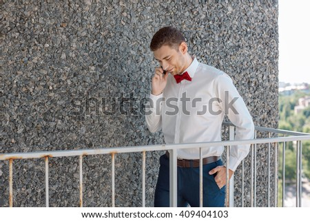 Portait of a young handsome man calling. Gorgeous guy on gray background - stock photo