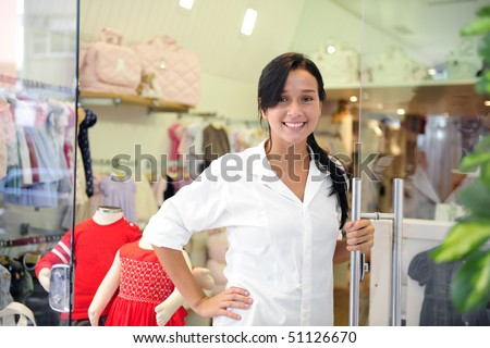 portait of small business owner: proud woman opening her  children clothing store - stock photo