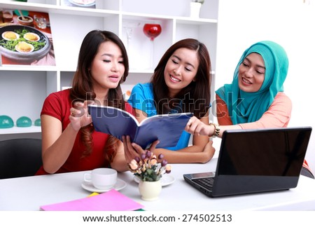 portait of three college students discussing about their lecture subject at livingroom - stock photo
