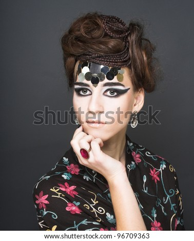 Portarit of young stylisn woman with creative visage. - stock photo