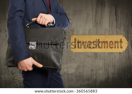 Portfolio investor. Businessman with briefcase on the background wall - stock photo