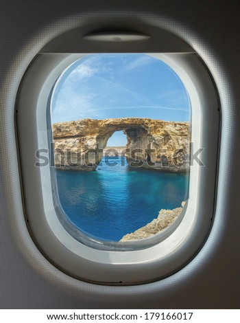 porthole and landmark, Azure Window, famous stone arch of Gozo island through the window of the plane against the blue sky on a clear day, Malta - stock photo