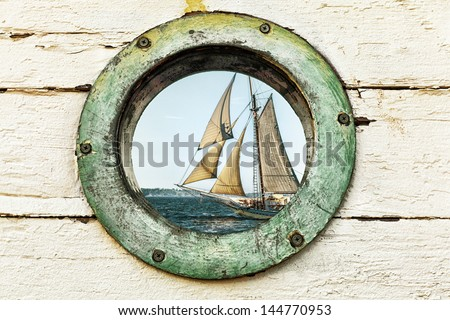 Porthole window looking out at an old sailing ship. Image has a vintage look and color palette. - stock photo