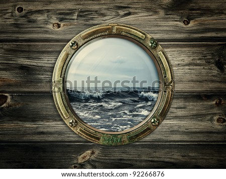 porthole with view at the sea - stock photo