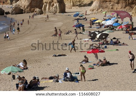 PORTIMAO, PORTUGAL - OCT 16: Tourists and locals enjoy the mild temperatures along the beach area known as Praia da Rocha on October 16, 2012 in Portimao, Portugal. - stock photo