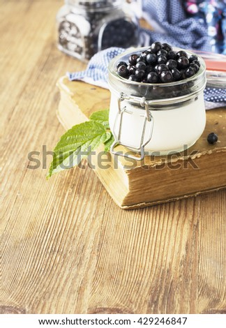 Portion breakfast in a glass jar with yogurt and fresh ripe blueberries on a wooden background. Breakfast included. Snack on the road. The concept of proper healthy diet. selective focus - stock photo