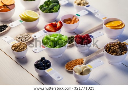 Portion cups of healthy ingredients on wooden table - stock photo