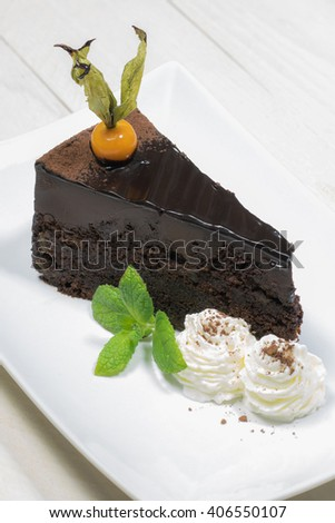 Portion of a sacher cake with physalis garnish and whipped cream - stock photo