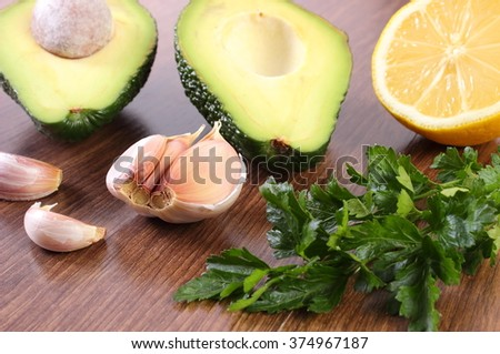 Portion of avocado, clove garlic, lemon and parsley, concept of healthy food, nutrition and omega fatty acids, ingredient of avocado paste or guacamole - stock photo