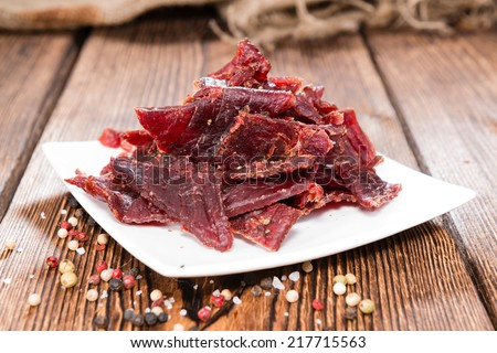 Portion of Beef Jerky on vintage wooden background - stock photo