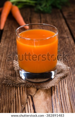 Portion of Carrot Juice on an old wooden table (selective focus) - stock photo