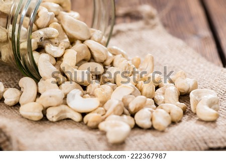 Portion of Cashew Nuts (close-up shot) on wooden background - stock photo