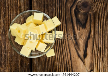 Portion of Cheese (close-up shot) on rustic wooden background - stock photo