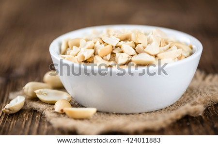Portion of chopped Peanuts (close-up shot; selective focus) on wooden background - stock photo