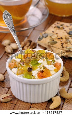 portion of cottage cheese with jam and marmalade slices, nuts, pistachios - stock photo