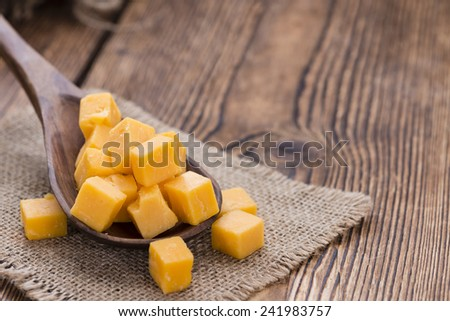 Portion of diced Cheddar on a Wooden Spoon (close-up shot) - stock photo