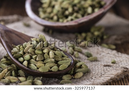 Portion of dried Cardamon Seeds (close-up shot) on wooden background - stock photo
