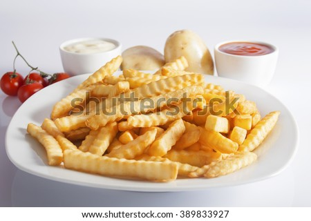 Portion of French fries (Crinkle-cut) deep fried, served on a white plate next to white bowls with mayonnaise and ketchup and fresh potato. - stock photo
