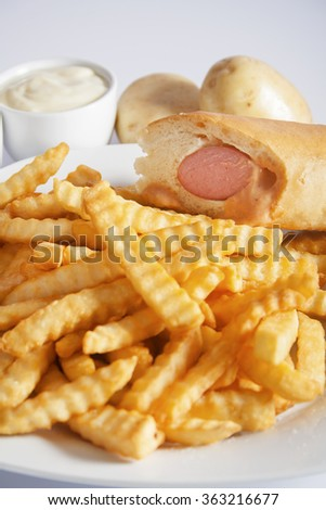 Portion of French fries (Crinkle-cut) deep fried, served on a white plate with hot dog next to white bowl with mayonnaise and fresh potato. - stock photo