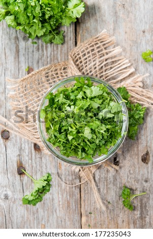 Portion of fresh cutted herbs (Parsley) in a small bowl - stock photo