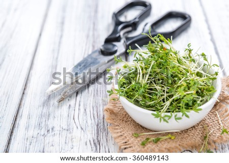Portion of fresh Garden Cress (detailed close-up shot) on wooden background - stock photo