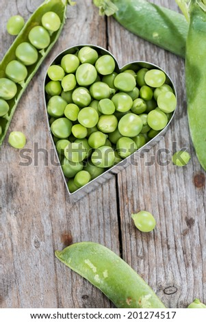 Portion of fresh harvested Peas on wooden background - stock photo