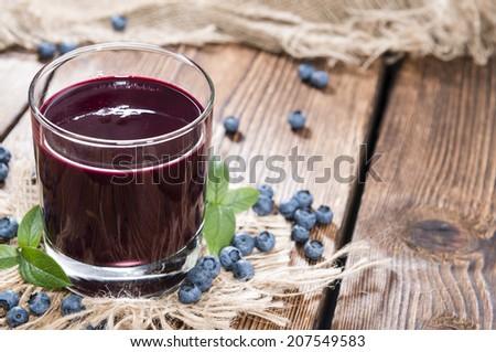 Portion of fresh homemade Blueberry Juice with some fresh fruits - stock photo