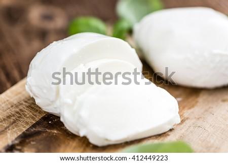Portion of fresh Mozzarella (close-up shot) on vintage wooden background (selective focus) - stock photo