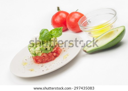 Portion of fresh salad with tomatoes, basil and avocado on light background - stock photo