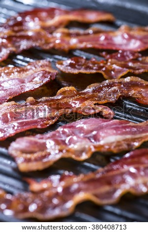 Portion of fried Bacon in a pan (close-up shot) - stock photo