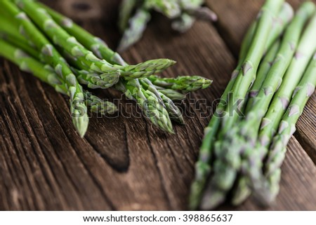 Portion of green Asparagus (close-up shot) on wooden background - stock photo