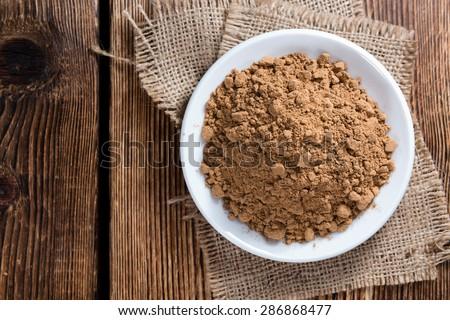Portion of Guarana Powder on dark wooden background (close-up shot) - stock photo
