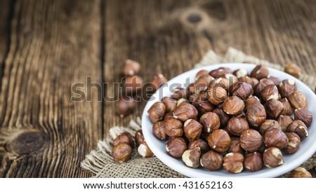 Portion of Hazelnuts (selective focus; close-up shot) on vintage background - stock photo