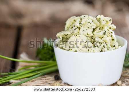 Portion of Herb Butter (with Chives, Basil, Oregano, Parsley and Rosemary) on rustic wooden background - stock photo