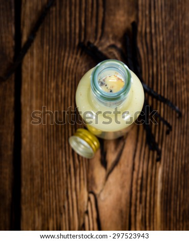 Portion of homemade Vanilla Milk (on rustic wooden background) - stock photo