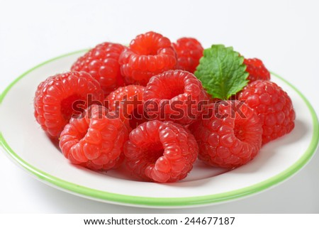 portion of juicy raspberries served on the plate - stock photo