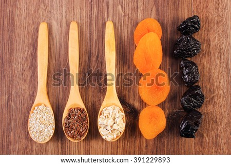 Portion of linseed, rye flakes and oat bran on spoon with dried fruits, concept of healthy nutrition and increase metabolism, ingredients with dietary fiber - stock photo