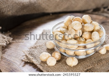 Portion of Macadamia nuts (roasted and salted) on wooden background - stock photo