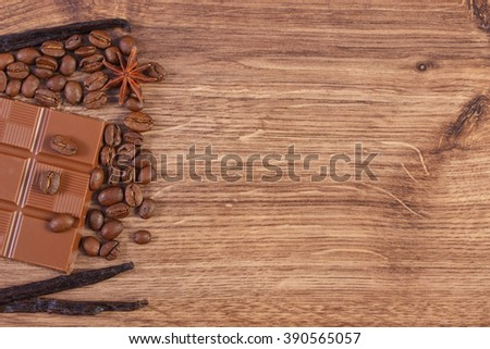 Portion of milk chocolate, fresh fragrant vanilla sticks pods, star anise and coffee grains on wooden background, copy space for text - stock photo