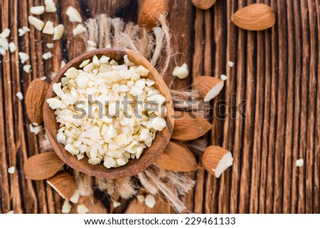 Portion of Minced Almonds (detailed close-up shot) on dark wooden background - stock photo