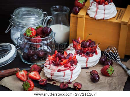 Portion of mini Pavlova meringue cake decorated with fresh strawberry and cherry - stock photo