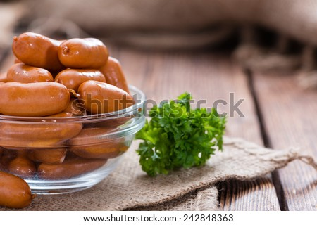 Portion of Mini Sausages (close-up shot) on rustic wooden background - stock photo