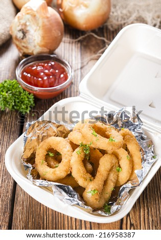 Portion of Onion Rings (homemade) with fresh herbs on  an old wooden table - stock photo