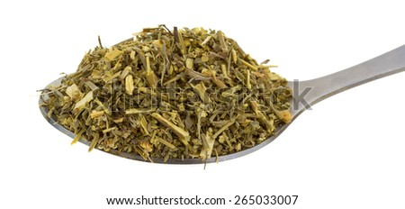 Portion of organic wormwood on an old spoon against a white background. - stock photo