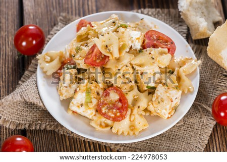 Portion of Pasta Salad with Farfalle, Cheese and Tomatoes (on wooden background) - stock photo