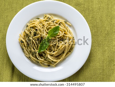 Portion of pasta with pesto sauce and basil leaf - stock photo