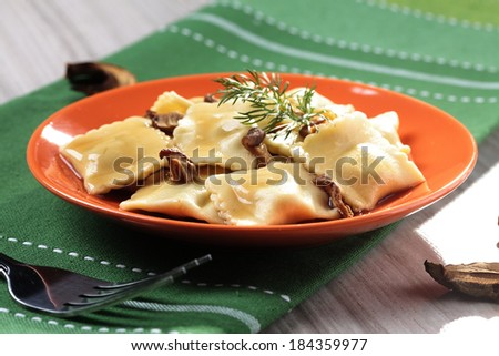 Portion of ravioli with mushrooms and sauerkraut on colored plate - stock photo
