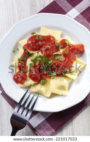 Portion of ravioli with tomato sauce on a white plate - stock photo