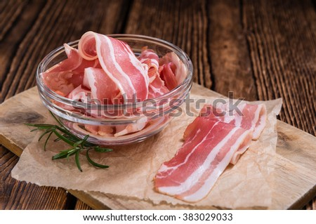 Portion of raw Bacon stripes on wooden background (selective focus) - stock photo
